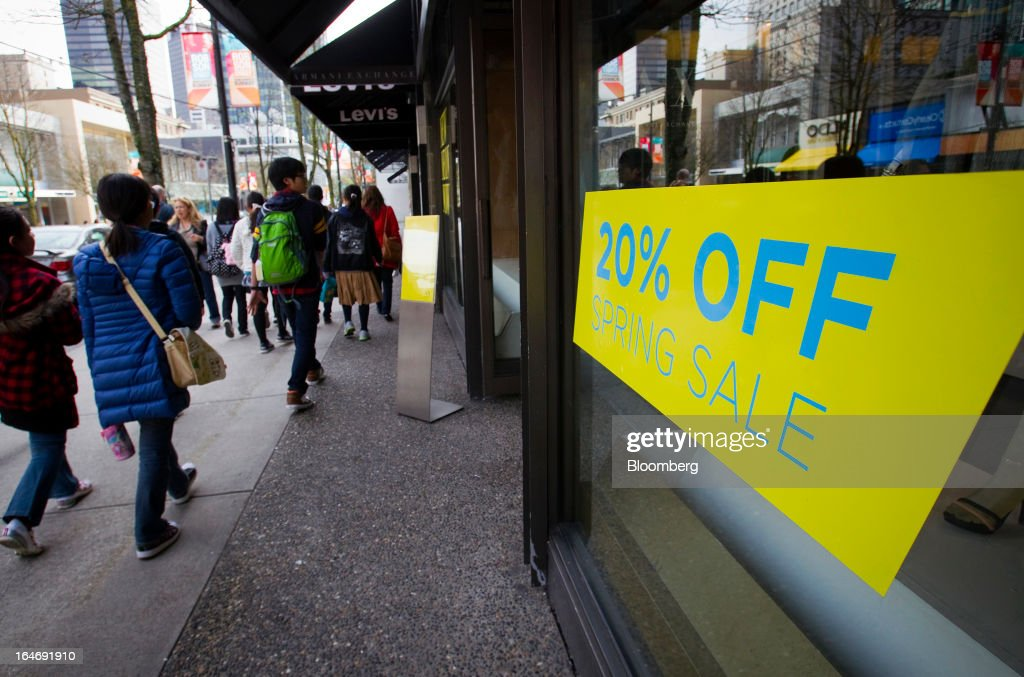 Pedestrians pass in front of store displaying a 20% off sign on Robson St. in Vancouver, British Columbia, Canada, on Monday, March 25, 2013. Statistics Canada (STCA) is scheduled to release consumer price index data on March 27, 2013. Photographer: Ben Nelms/Bloomberg via Getty Images