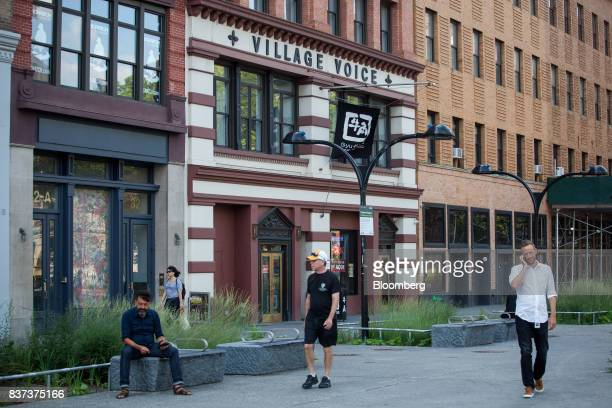 Pedestrians pass in front of the former headquarters for The Village Voice in the East Village neighborhood of New York US on Tuesday Aug 22 2017...
