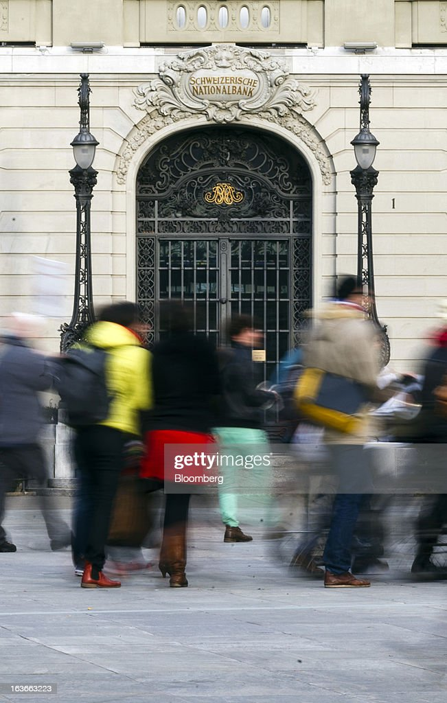 Pedestrians pass in front of the headquarters of the Swiss National Bank (SNB), Switzerland's central bank, in Bern, Switzerland, on Tuesday, March 12, 2013. The Swiss central bank pledged to keep up its defense of the franc cap after almost doubling its currency holdings to shield the country from the fallout caused by the euro zone's crisis. Photographer: Valentin Flauraud/Bloomberg via Getty Images