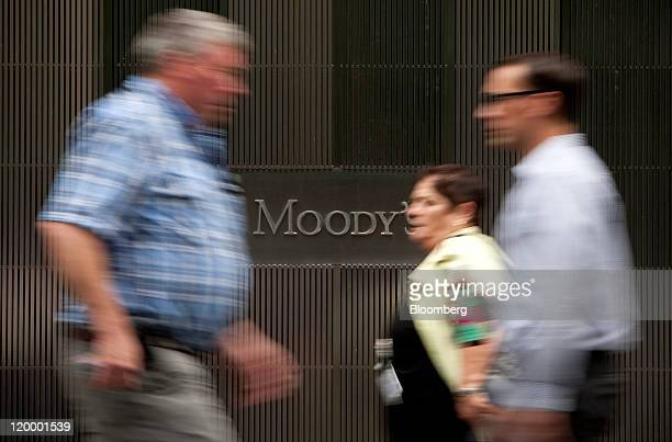 Pedestrians pass in front of the Moody's Investors Service Inc headquarters in New York US on Thursday July 28 2011 Moody's Investors Service...