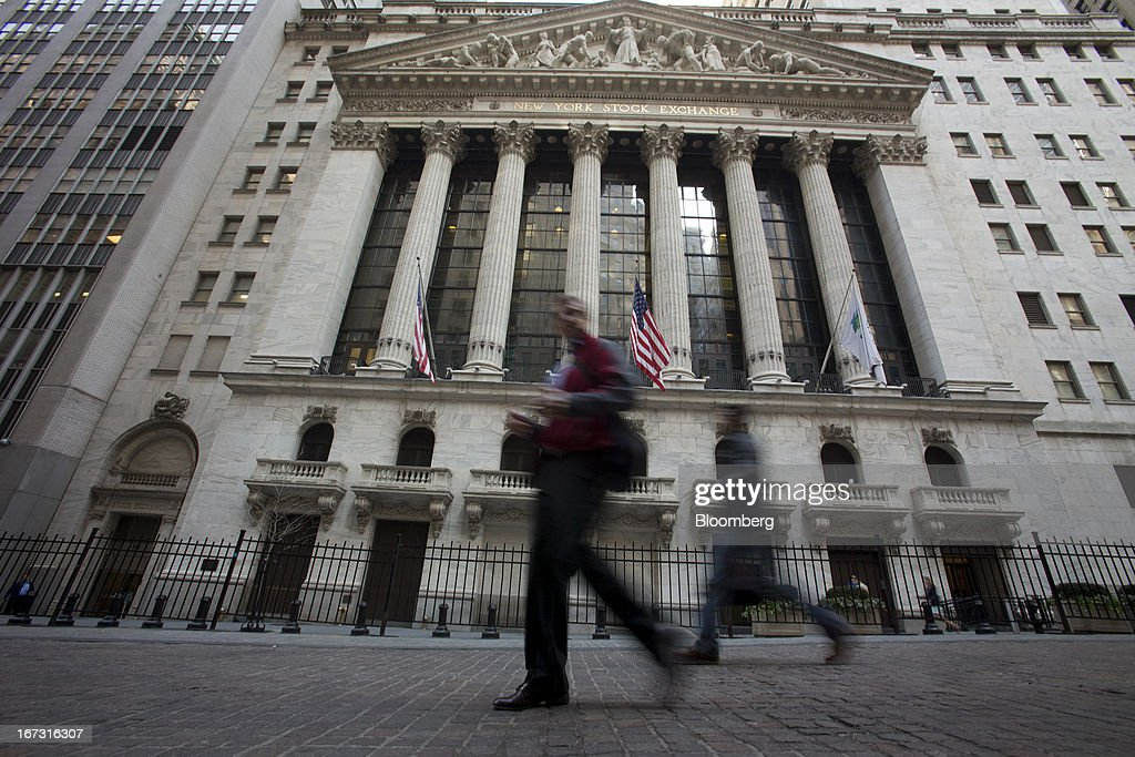 Pedestrians pass in front of the New York Stock Exchange (NYSE) in New York, U.S., on Wednesday, April 24, 2013. U.S. stocks were little changed, after the Standard & Poor's 500 Index gained for a third day, as investors watched earnings at companies from Boeing Co. to Apple Inc. Photographer: Scott Eells/Bloomberg via Getty Images