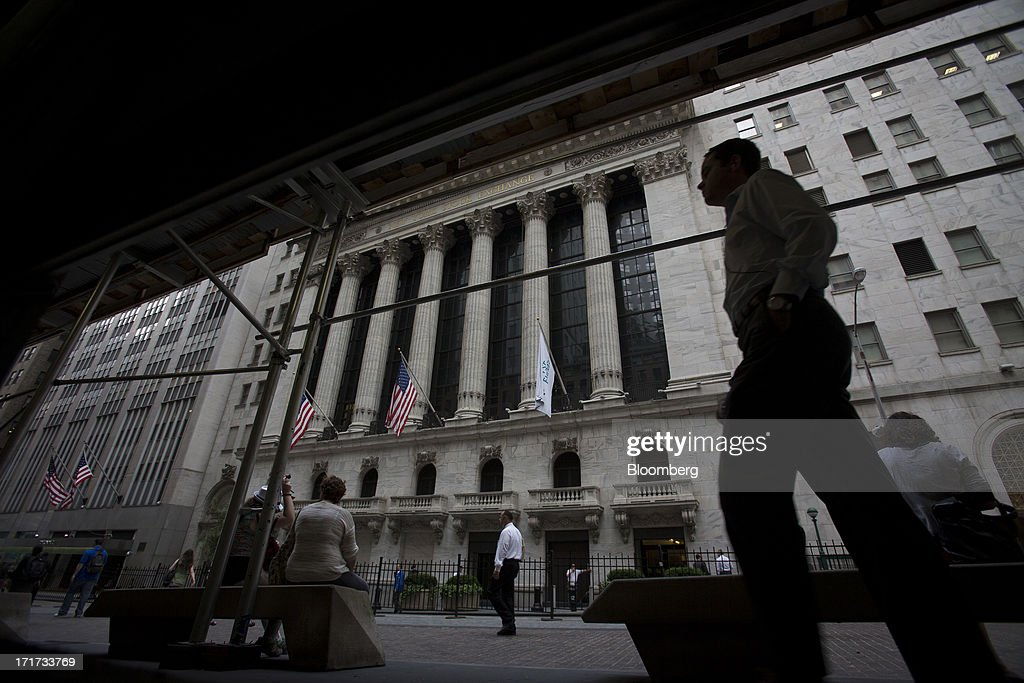 Pedestrians pass in front of the New York Stock Exchange (NYSE) in New York, U.S., on Friday, June 28, 2013. U.S. stocks fell, after the biggest three-day rally since January for the Standard & Poor's 500 Index, before data on consumer sentiment and business activity as investors weighed statements from Federal Reserve officials. Photographer: Scott Eells/Bloomberg via Getty Images