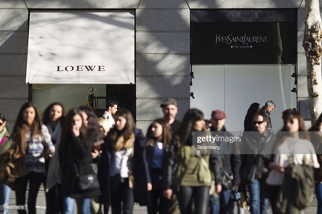 Pedestrians pass Loewe AG and Yves Saint Laurent Groupe SA luxury stores in Madrid, Spain, on Wednesday, Jan. 30, 2013. Spain's recession deepened more than economists forecast in the fourth quarter as the government's struggle to rein in the euro region's second-largest budget deficit weighed on domestic demand. Photographer: Angel Navarrete/Bloomberg via Getty Images