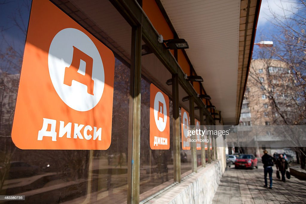 Pedestrians pass logos in the windows of a Dixy supermarket operated by OAO Dixy Group in Moscow, Russia, on Tuesday, April 8, 2014. Suppliers suffering from ruble depreciation this quarter are urging retailers to increase prices. Photographer: Andrey Rudakov/Bloomberg via Getty Images