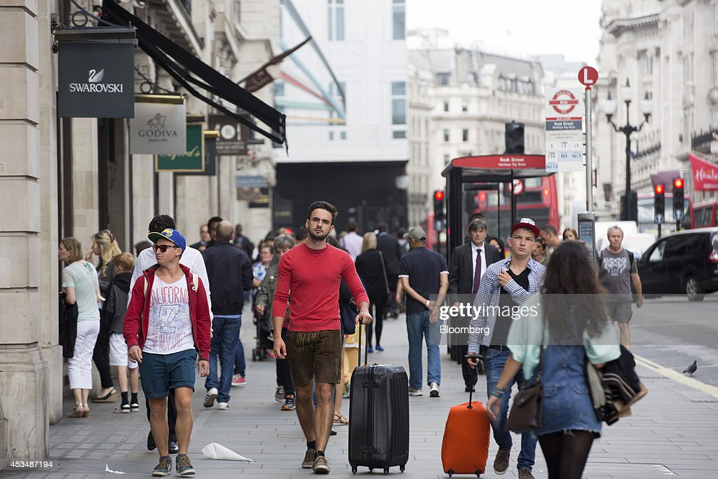Pedestrians pass luxury stores located inside commercial real estate buildings that form part of the Pollen Estate, on Regent Street in London, U.K., on Monday, Aug. 11, 2014. Norway's sovereign wealth fund, Norges Bank Investment Management, the world's largest, bought a stake in the Pollen Estate in London's Mayfair district for 343 million pounds ($576 million), expanding its property holdings in the U.K. capital. Photographer: Jason Alden/Bloomberg via Getty Images