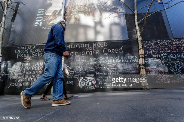Pedestrians pass messages of support and protest scrawled onto the hording of a construction site at Martin Place on August 6 2017 in Sydney...