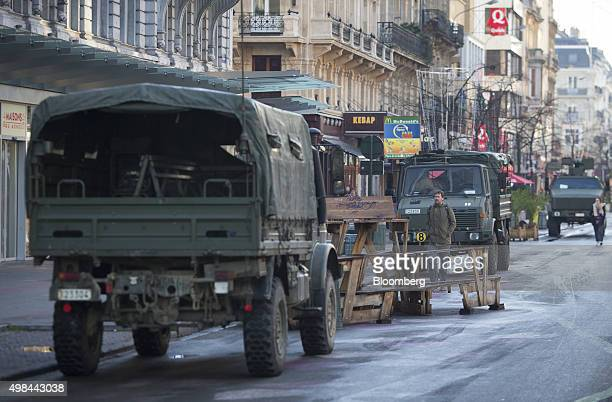 Pedestrians pass military trucks parked on a street near Grand Place square in Brussels Belgium on Monday Nov 23 2015 The search for a key suspect in...