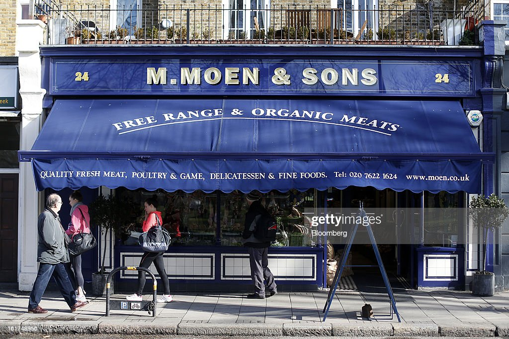 Pedestrians pass M.Moen & Sons butcher's shop in the Clapham district of London, U.K., on Friday, Feb. 15, 2013. While there's no evidence yet that consumer beef demand has slowed in the U.K., customers probably will spend more on higher quality cuts at meat counters or buy from independent butchers, Nick Allen, the executive director of the Agriculture & Horticulture Development Board's beef and lamb unit, known as Eblex, said. Photographer: Simon Dawson/Bloomberg via Getty Images
