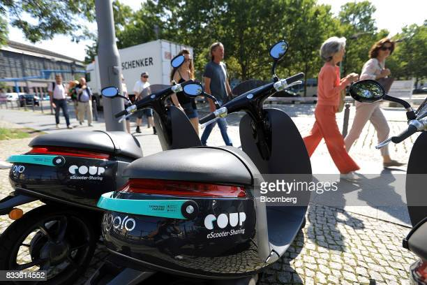 Pedestrians pass parked Coup eScooter electric hire vehicles operated by Robert Bosch GmbH in Berlin Germany on Thursday Aug 17 2017 Coup is one of...