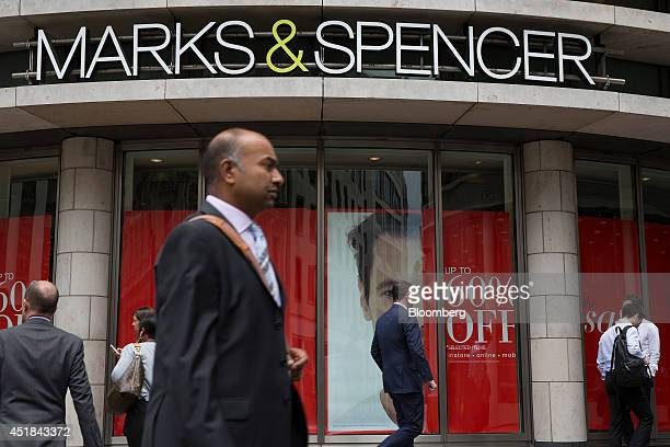 Pedestrians pass posters advertising a sale on clothing in the window display of a Marks Spencer retail store operated by Marks Spencer Group Plc in...