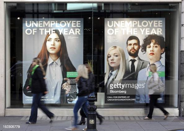 Pedestrians pass posters for Benetton Group SpA's new advertising campaign 'Unemployee of the Year' as they hang in the window of the company's store...