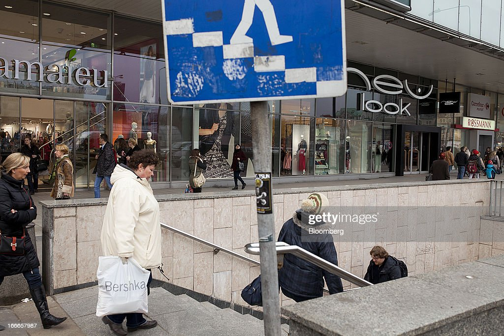 Pedestrians pass retail stores in a shopping mall in Warsaw, Poland, on Thursday, April 11, 2013. Poland's central bank kept interest rates unchanged at a record-low 3.25 percent yesterday. Photographer: Bartek Sadowski/Bloomerg
