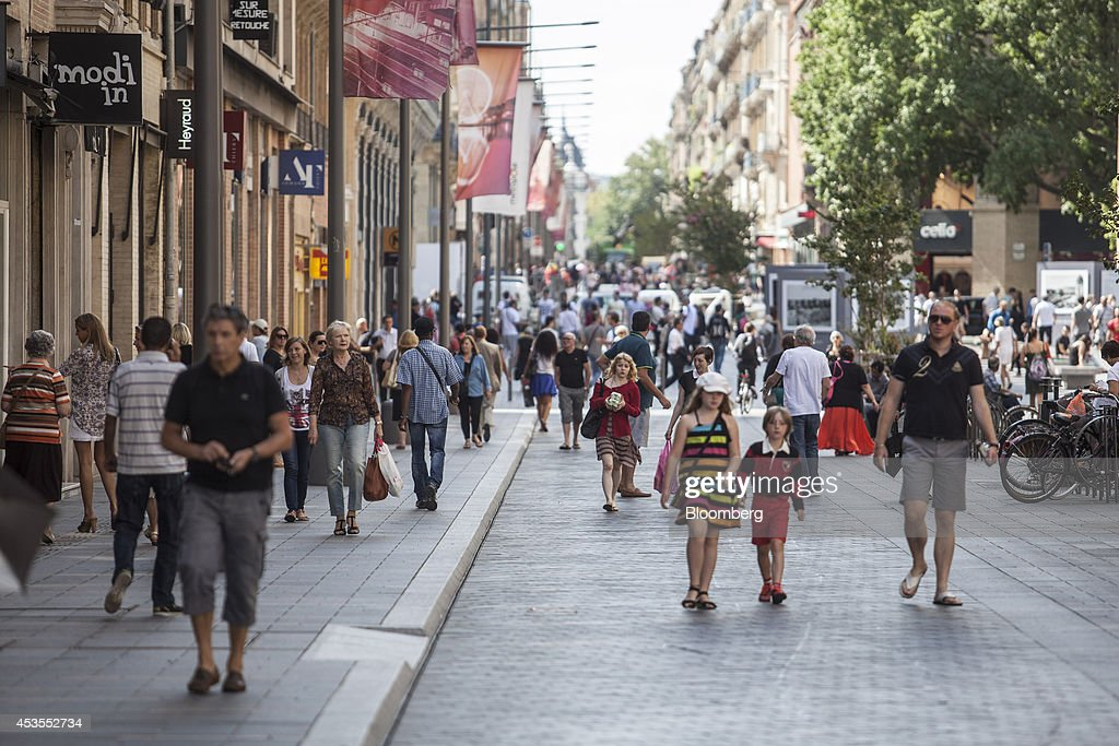 Pedestrians pass retail stores on the main shopping street in Toulouse, France, on Tuesday, Aug. 12, 2014. The euro traded 0.3 percent from a nine-month low before reports this week that may show growth in the region weakened and inflation slowed, adding to signs the bloc's economy is struggling to recover. Photographer: Balint Porneczi/Bloomberg via Getty Images