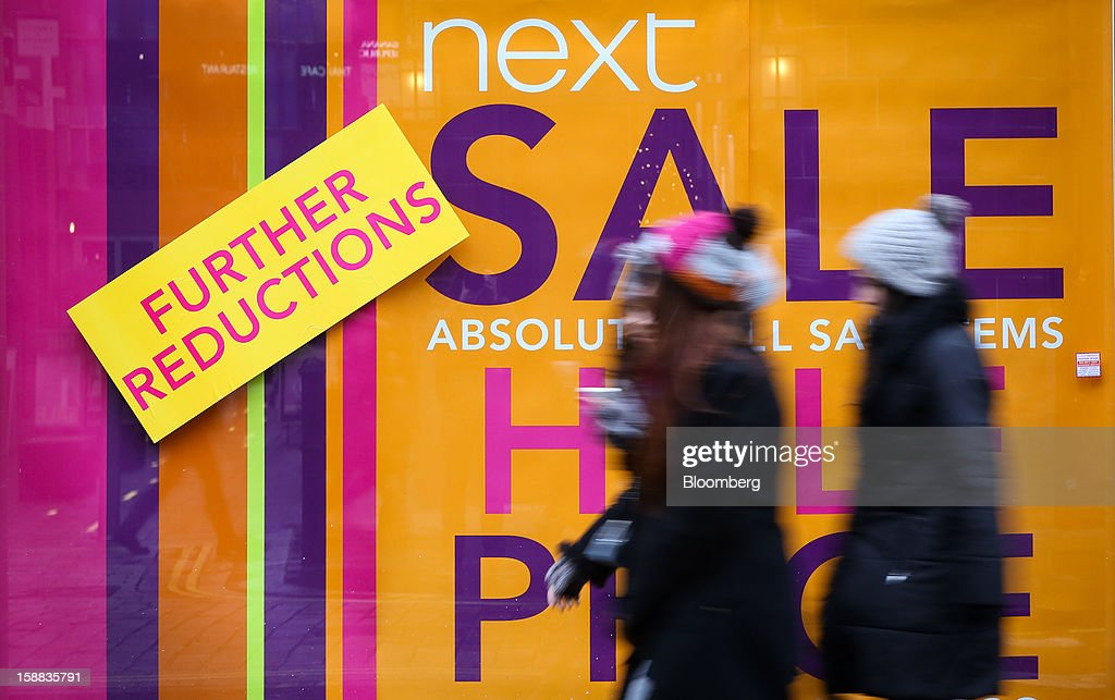 Pedestrians pass sale signs in the window of a Next Plc clothing store in the Covent Garden district of London, U.K., on Monday, Dec. 31, 2012. The number of Britons making shopping trips for post-holiday bargains barely increased on the day after Christmas as more people sought discounts online. Photographer: Jason Alden/Bloomberg via Getty Images