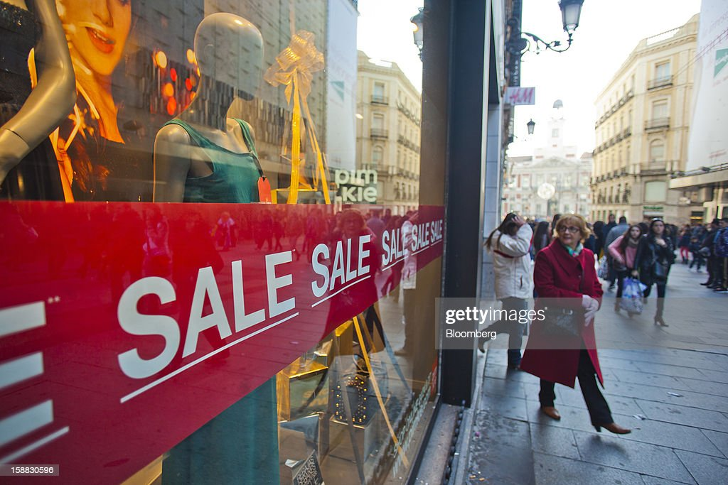 Pedestrians pass sale signs in the window of a store in central Madrid, Spain, on Saturday, Dec. 29, 2012. Spain's economic activity kept falling in the fourth quarter, Bank of Spain says. Photographer: Angel Navarrete/Bloomberg via Getty Images