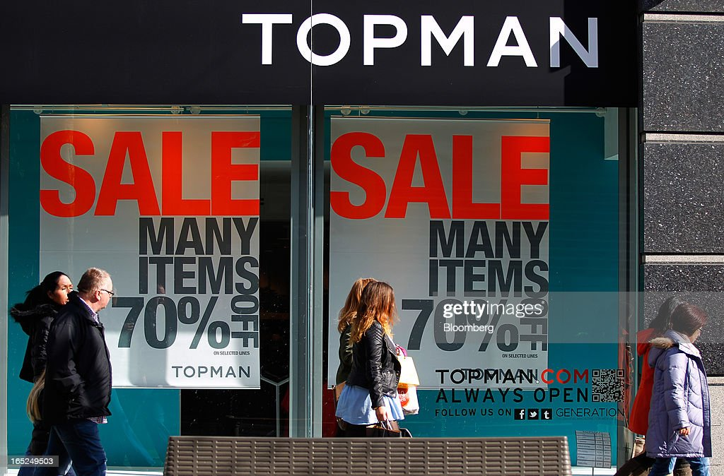 Pedestrians pass sales advertisements in the windows of a Topman fashion store, operated by Arcadia Group Ltd., in Manchester, U.K., on Monday, April 1, 2013. U.K. retail sales unexpectedly stagnated in March in a sign that consumer spending remains under pressure from higher energy bills and weak wage growth. Photographer: Paul Thomas/Bloomberg via Getty Images