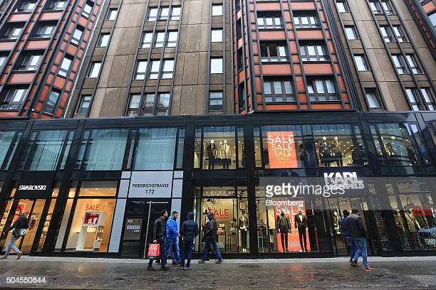 Pedestrians pass sales promotion signs in the windows of a Swarovski luxury jewelry store left and a Karl Lagerfeld fashion outlet in Berlin Germany...