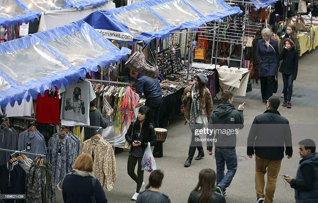 Pedestrians pass stalls selling a range of goods including clothing and jewelry at Old Spitalfields Market in London, U.K., on Wednesday, May 29, 2013. Annual U.K. consumer-price inflation slowed to 2.4 percent last month from 2.8 percent in March, the Office for National Statistics said May 21. Photographer: Chris Ratcliffe/Bloomberg via Getty Images