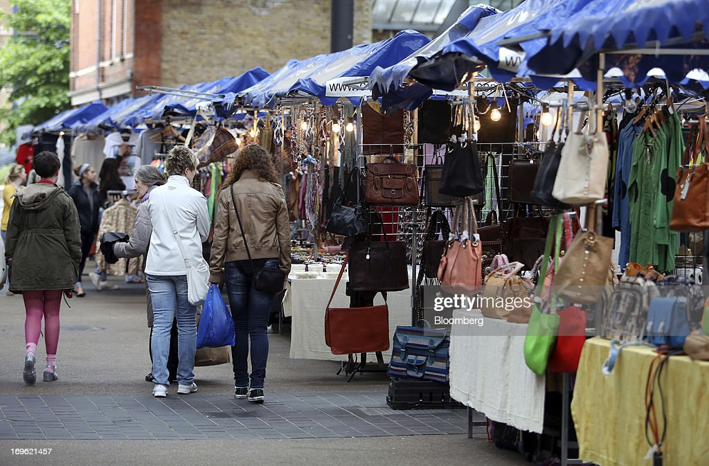 Pedestrians pass stalls selling bags and jewelry in Old Spitalfields Market in London, U.K., on Wednesday, May 29, 2013. Annual U.K. consumer-price inflation slowed to 2.4 percent last month from 2.8 percent in March, the Office for National Statistics said May 21. Photographer: Chris Ratcliffe/Bloomberg via Getty Images