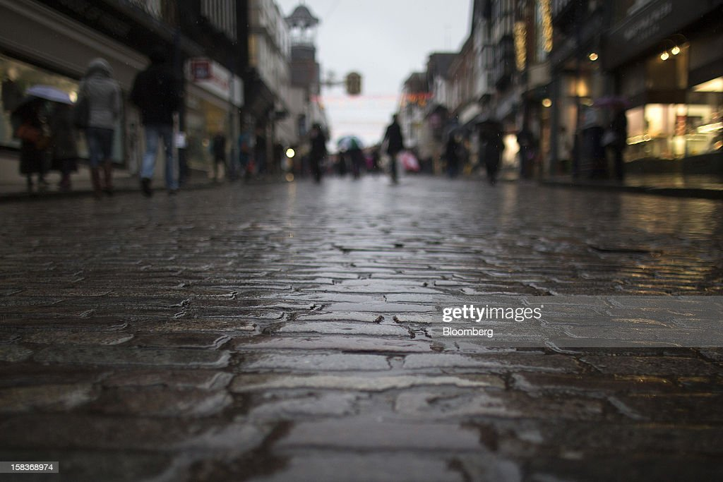 Pedestrians pass stores as they walk along a cobbled street in Guildford, U.K., on Friday, Dec. 14, 2012. Standard & Poor's lowered its outlook on Britain's top credit rating to negative, citing weak economic growth and a worsening debt profile. Photographer: Simon Dawson/Bloomberg via Getty Images