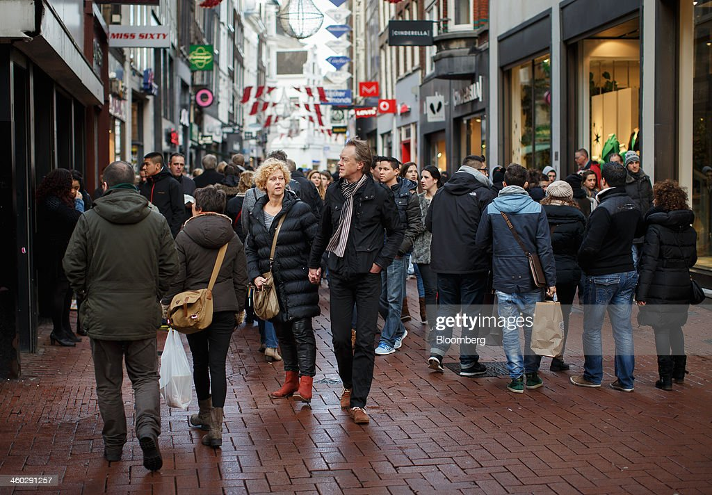 Pedestrians pass stores on a retail street in Amsterdam, Netherlands, on Thursday, Jan. 2, 2014. The Netherlands will grow by 0.5 percent in 2014 as the world economy improves and consumer confidence picks up, the country's central bank forecast Dec. 9. Photographer: Jasper Juinen/Bloomberg via Getty Images