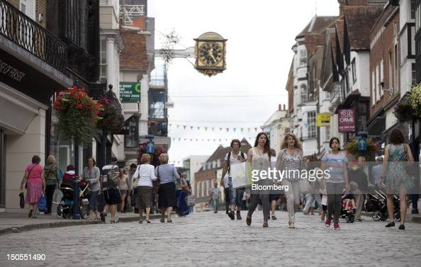Pedestrians pass stores on the High Street in Guildford UK on Tuesday Aug 21 2012 UK retail sales unexpectedly rose in July as promotions helped to...
