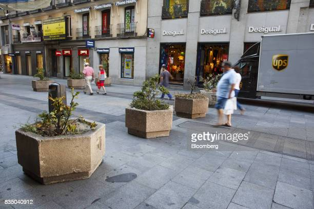Pedestrians pass street furniture positioned to prevent vehicle access to Preciados street in Madrid Spain on Friday Aug 18 2017 Terrorists behind...