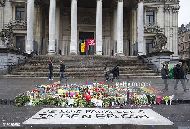 Pedestrians pass the Brussels stock exchange operated by Euronext NV as flowers and floral tributes sit on Beursplein square in Brussels Belgium on...