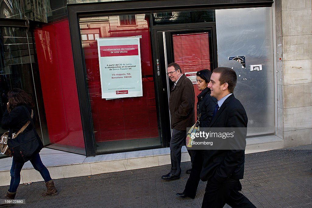 Pedestrians pass the closed down offices of a former Banco Pastor SA bank branch in Barcelona, Spain, on Tuesday, Jan. 8, 2013. Banco Santander SA, Spain's biggest lender, will offer 263 million euros ($345 million) in stock to buy out minority investors in its Banco Espanol de Credito SA retail unit and close 700 local branches to cut costs. Photographer: David Ramos/Bloomberg via Getty Images