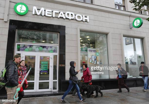 Pedestrians pass the entrance to a MegaFon PJSC mobile phone store in Moscow Russia on Tuesday Aug 29 2017 MegaFon considers various alternatives for...