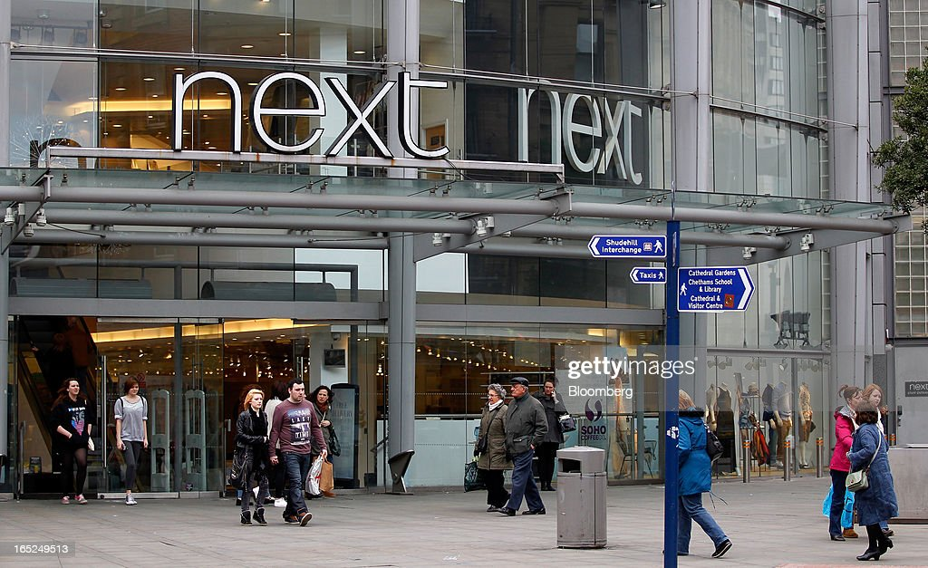 Pedestrians pass the entrance to a Next Plc store in Manchester, U.K., on Monday, April 1, 2013. U.K. retail sales unexpectedly stagnated in March in a sign that consumer spending remains under pressure from higher energy bills and weak wage growth. Photographer: Paul Thomas/Bloomberg via Getty Images