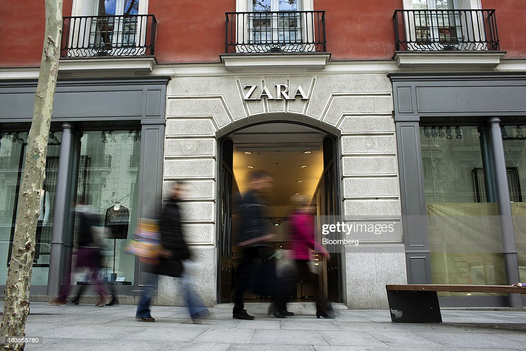 Pedestrians pass the entrance to a Zara fashion store, operated by Inditex SA, in Madrid, Spain, on Tuesday, March 12, 2013. Europe's richest man, Amancio Ortega, the 76-year-old founder of Inditex SA, the world's biggest clothing retailer and owner of the Zara clothing chain, is No. 3 on Standard & Poor's 500 Index with a net worth of $57.4 billion, $4.9 billion ahead of Warren Buffett, 82. Photographer: Angel Navarrete/Bloomberg via Getty Images