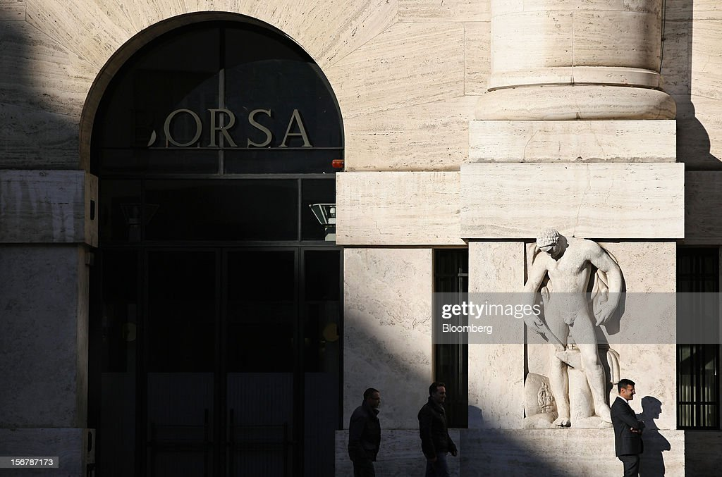 Pedestrians pass the entrance to the Borsa Italiana, Italy's stock exchange and part of the London Stock Exchange Group Plc, in Milan, Italy, on Tuesday, Nov. 20, 2012. Telecom Italia SpA said it is still reviewing the possible spinoff of its fixed-line network and the company's board will discuss the outcome of its analysis on Dec. 6. Photographer: Alessia Pierdomenico/Bloomberg via Getty Images