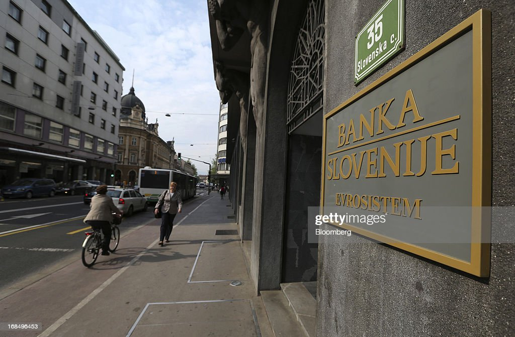 Pedestrians pass the entrance to the central bank, also known as Banka Slovenije, in Ljubljana, Slovenia, on Friday, May 10, 2013. The Adriatic nation is seeking to fix its ailing lenders with a cash injection of at least 900 million euros ($1.17 billion) after Cyprus's bailout focused investors on countries with weak banking industries. Photographer: Chris Ratcliffe/Bloomberg via Getty Images