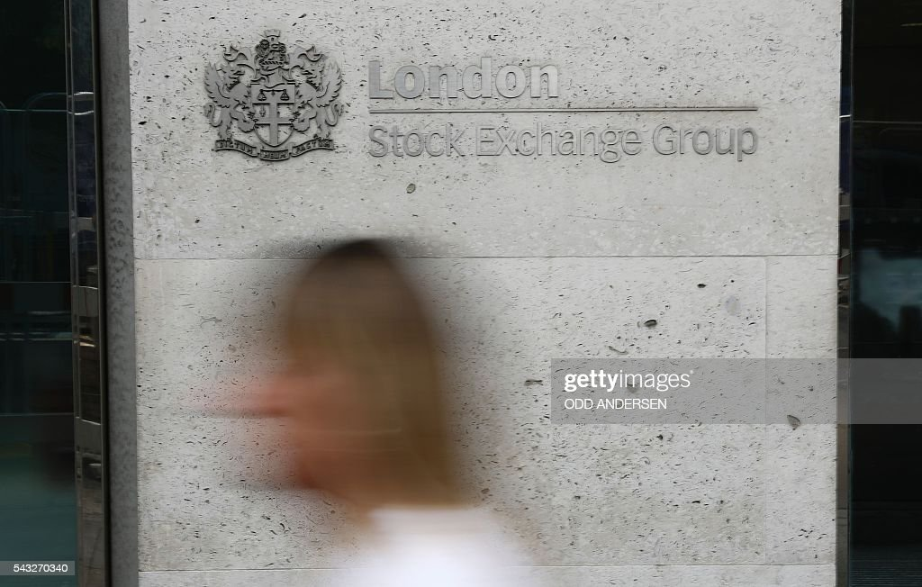 Pedestrians pass the entrance to the London Stock Exchange in central london on June 27, 2016. Shares in banks, airlines and property companies plunged on the London stock exchange Monday as investors singled out the three sectors as being the most vulnerable to Britain's decision to leave the EU. / AFP / ODD