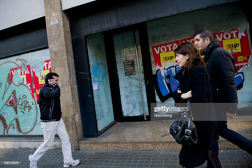 Pedestrians pass the grafitti-covered windows of a closed down CatalunyaCaixa bank branch in Barcelona, Spain, on Tuesday, Jan. 8, 2013. Banco Santander SA, Spain's biggest lender, will offer 263 million euros ($345 million) in stock to buy out minority investors in its Banco Espanol de Credito SA retail unit and close 700 local branches to cut costs. Photographer: David Ramos/Bloomberg via Getty Images