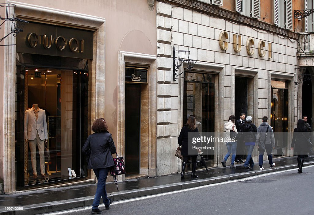 Pedestrians pass the Gucci store, a luxury unit of France's PPR SA, in Rome, Italy, on Monday, Nov. 19, 2012. PPR SA, the French owner of the Gucci and Puma brands, said it's confident of revenue and profit growth in 2012. Photographer: Alessia Pierdomenico/Bloomberg via Getty Images