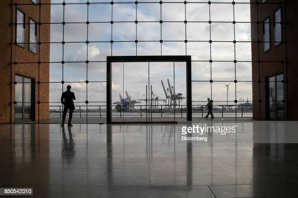 Pedestrians pass the HHLA Container Terminal Tollerort as shipping cranes stand on the dockside beyond at the Port of Hamburg in Hamburg Germany on...