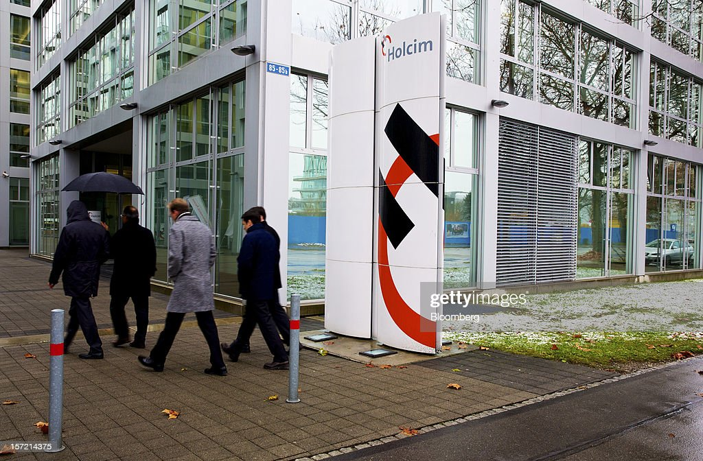 Pedestrians pass the Holcim Ltd.'s offices in Zurich, Switzerland, on Thursday, Nov. 29, 2012. Holcim Ltd., the world's largest cement maker, is considering disposals as Fontana deals with a greater-than-expected slowdown in Europe. Photographer: Gianluca Colla/Bloomberg via Getty Images