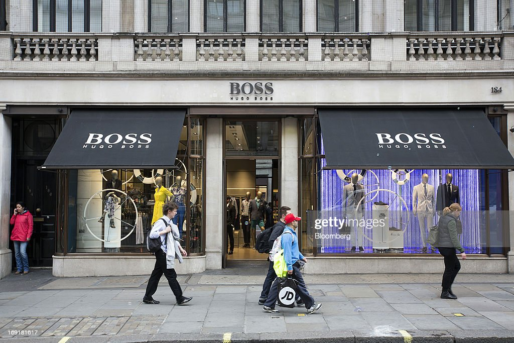 Pedestrians pass the Hugo Boss AG store on Regent Street in London, U.K. on Tuesday, May 21, 2013. Hugo Boss AG reiterated its earnings forecast for the year after the German luxury-clothing maker said its retail business increased sales by 14 percent in the first quarter as it opened more outlets. Photographer: Simon Dawson/Bloomberg via Getty Images