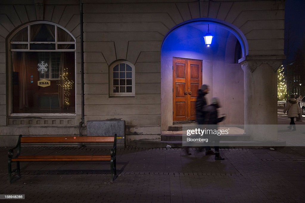 Pedestrians pass the illuminated entrance to a building at night in Reykjavik, Iceland, on Tuesday, Jan. 1, 2013. Iceland's inflation rate eased in December as central bank efforts to stabilize the krona with interest rate increases paid off. Photographer: Arnaldur Halldorsson/Bloomberg via Getty Images