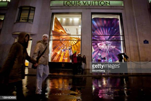 Pedestrians pass the illuminated window display of a Louis Vuitton store operated by LVMH Moet Hennessy Louis Vuitton SA on the ChampsElysees in...