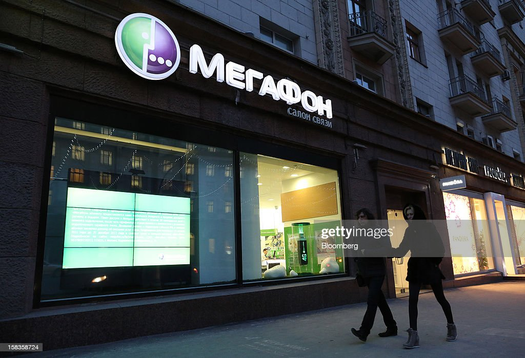 Pedestrians pass the illuminated window of an OAO MegaFon mobile phone store in Moscow, Russia, on Thursday, Dec. 13, 2012. OAO MegaFon and its main shareholder billionaire Alisher Usmanov bought 50 percent of Euroset Holding NV in a deal that gives Russia's biggest handset retailer an enterprise value of $2.3 billion. Photographer: Andrey Rudakov/Bloomberg via Getty Images