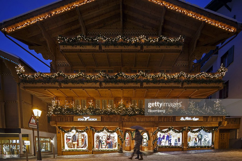 Pedestrians pass the illuminated windows of a fashion store on the promenade in Gstaad, Switzerland, on Saturday, Jan. 19, 2013. Options traders are pushing the cost of bearish wagers on Swiss shares to the lowest level in almost seven years amid optimism a decline in the franc versus the euro will benefit the nation's exporters. Photographer: Valentin Flauraud/Bloomberg via Getty Images