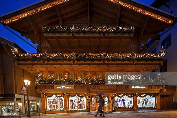 Pedestrians pass the illuminated windows of a fashion store on the promenade in Gstaad Switzerland on Saturday Jan 19 2013 Options traders are...