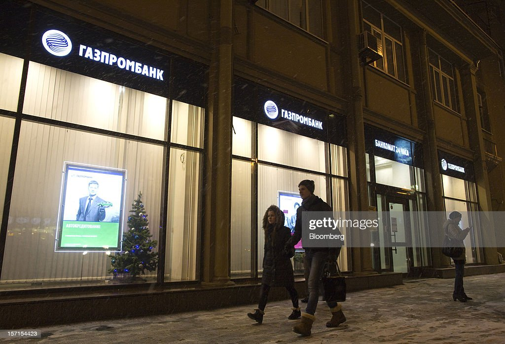 Pedestrians pass the illuminated windows of an OAO Gazprombank in Moscow, Russia, on Wednesday, Nov. 28, 2012. Bank Rossii proposes government create rule limiting increases of budget funds held at central bank, RIA Novosti reports, citing First Deputy Chairman Alexey Ulyukayev. Photographer: Andrey Rudakov/Bloomberg via Getty Images