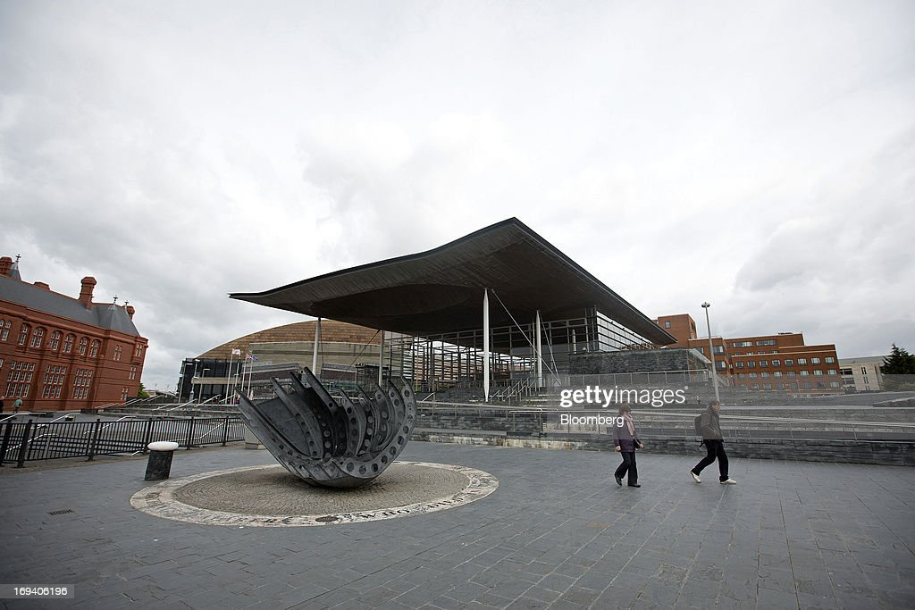 Pedestrians pass the 'Merchant Seafarer's War Memorial' sculpture, by artiust Brian Fell, as they walk near the Senedd, or National Assembly for Wales government building in Cardiff, U.K. on Thursday, May 23, 2013. Bank of England Markets Director Paul Fisher said policy makers must continue to provide support to the British economy so that companies and consumers have room to reduce debts and rebuild confidence. Photographer: Simon Dawson/Bloomberg via Getty Images