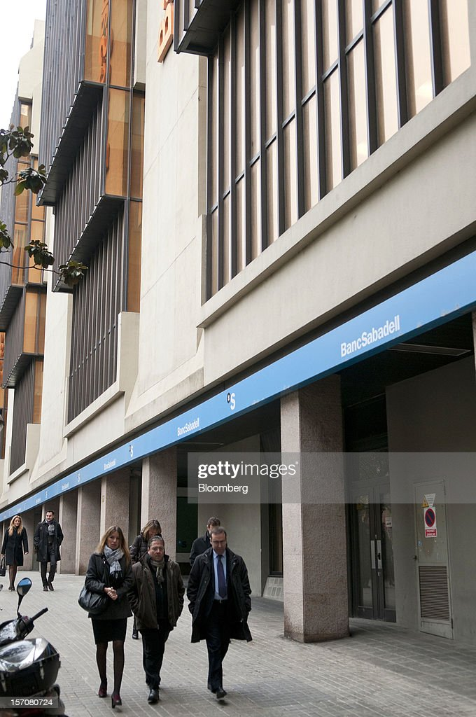 Pedestrians pass the offices of Banco Sabadell SA in Sabadell, Spain, on Wednesday, Nov. 28, 2012. Spanish banks getting European aid will shrink their balance sheets more than 60 percent, the European Commission said, as BFA-Bankia, the biggest rescued lender, expects to lose 19 billion euros ($25 billion) this year. Photographer: Stefano Buonamici/Bloomberg via Getty Images