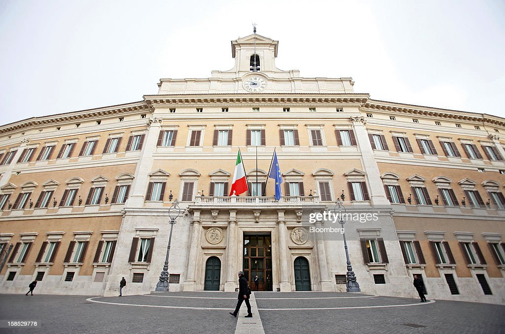 Pedestrians pass the Palazzo Montecitorio, Italy's parliament building and office of the Chamber of Deputies, in Rome, Italy, on Tuesday, Dec. 18, 2012. Italian Prime Minister Mario Monti, who is under pressure from euro-area and business leaders to enter the Italian election campaign, plans to quit once parliament passes his budget this week. Photographer: Alessia Pierdomenico/Bloomberg via Getty Images