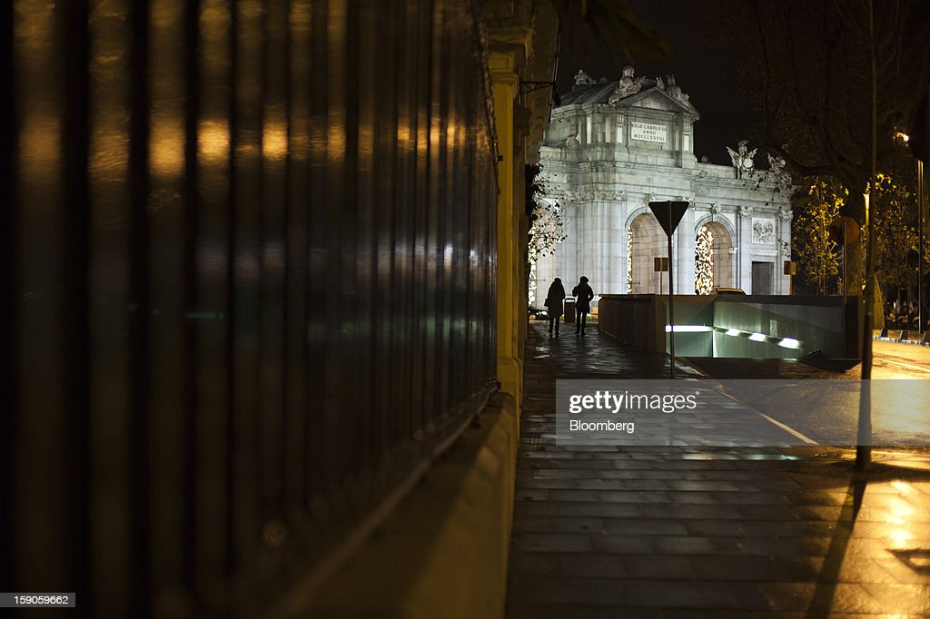 Pedestrians pass the Puerta de Alcala monument illuminated at night in Madrid, Spain, on Sunday, Jan. 6, 2013. In December, the Spanish parliament passed an energy law that imposed a 7 percent tax on electricity generation from Jan. 1 to plug the deficit. Photographer: Angel Navarrete/Bloomberg via Getty Images